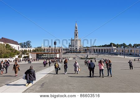 Sanctuary of Fatima, Portugal, March 07, 2015 - Devout walking the Penitential Path on knees and pilgrims. Our Lady of Rosary Basilica and Chapel of Apparitions at the back.