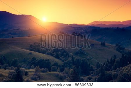 Great hills glowing by warm sunlight at twilight. Dramatic scene. Colorful sky. Carpathian, Ukraine, Europe. Beauty world. Retro and vintage style, soft filter. Instagram toning effect.