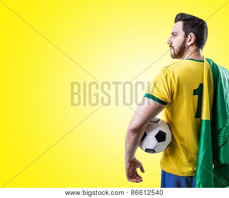 Brazilian soccer player holding the flag of Brazil and a ball on yellow background