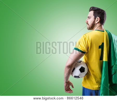 Brazilian soccer player holding the flag of Brazil and a ball on green background