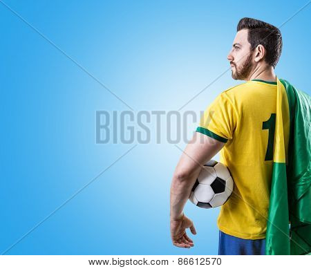 Brazilian soccer player holding the flag of Brazil and a ball on blue background