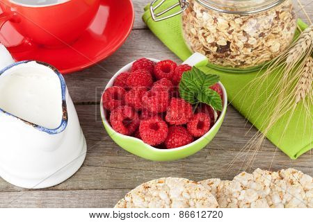 Healthy breakfast with muesli, berries and milk. On wooden table