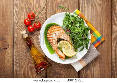Grilled salmon, salad and condiments on wooden table. Top view