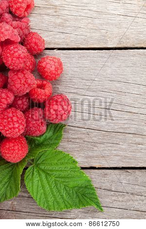 Fresh ripe raspberries on wooden table background with copy space
