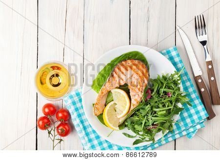 Grilled salmon and whtie wine on wooden table. Top view with copy space