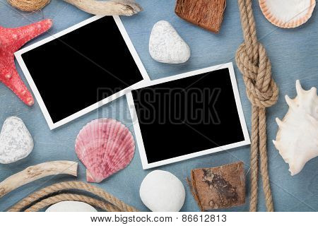 Blank photo frames with seashells, ship rope, sea stones over blue wooden background