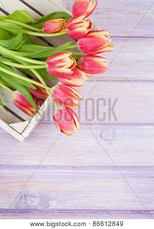 Orange tulips over wooden table. Top view with copy space