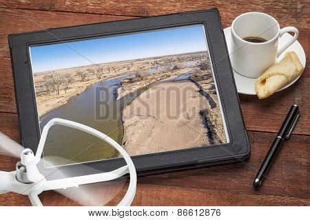 Reviewing aerial pictures of South Platte River in Colorado on digital tablet with a drone rotor and cup of coffee - aerial landscape photography concept. Screen picture copyright by the photographer.