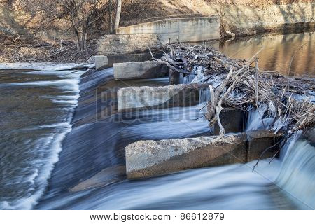 old river dam diverting water for farmland irrigation, Cache la Poudre RIver in Fort Collins, Colorado, winter or early spring scenery