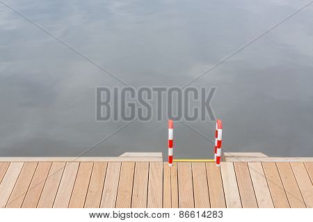 Wooden Pier And Ladder By The Water.