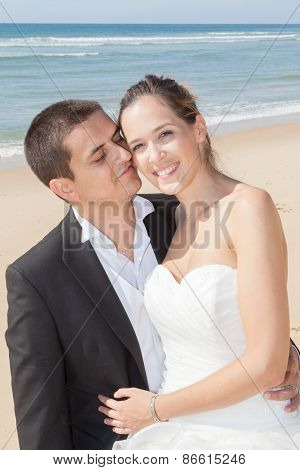 A Married Couple, Bride And Groom, Together In Summer  On A Beautiful Beach
