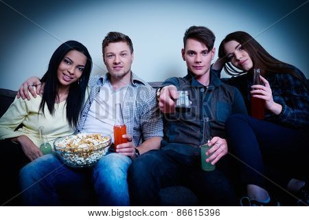 Multinational friends watching movie at home
