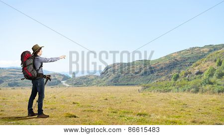 Young man hiker with backpack walking on route