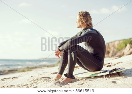 A young man sitting on his surfboard on the sand