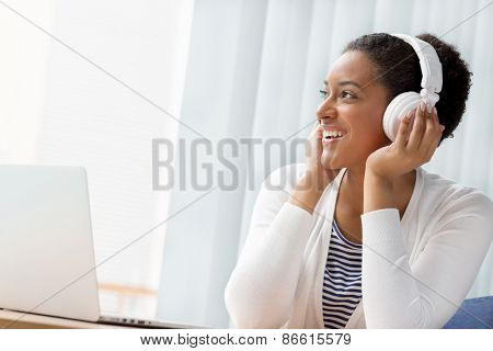Woman in headphones sitting at desk in office