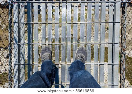Looking down on a suspension bridge over a river in Nepal
