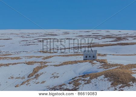Small hut on snow hill, Iceland
