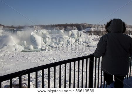 Tourist Looking At The Frozen  American Falls At Niagara During Winter