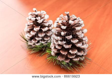 Two fir cones on the wooden table