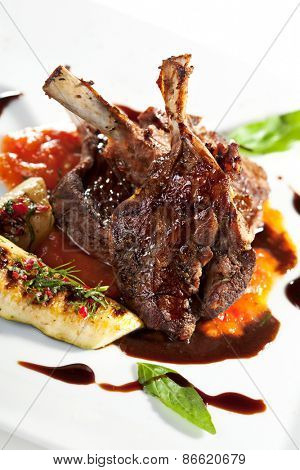 Roasted Lamb Chops on Tomato Sauce Garnished with Vegetables and Basil