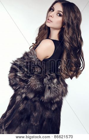 sexy woman with dark hair in luxurious fur coat