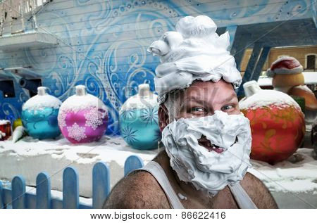 Strange smiling man with shaving foam on his face and on his head over winter background