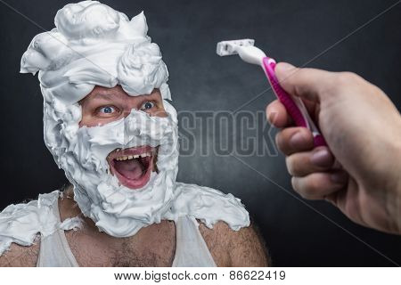 Surprised man with shaving foam on his face over grey background