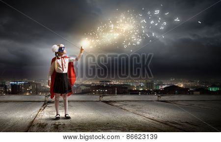Cute girl of school age in superhero costume with balloon in hand