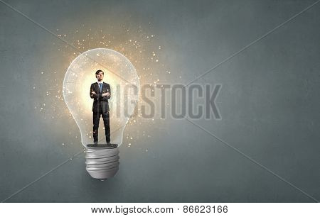 Young businessman standing inside of light bulb