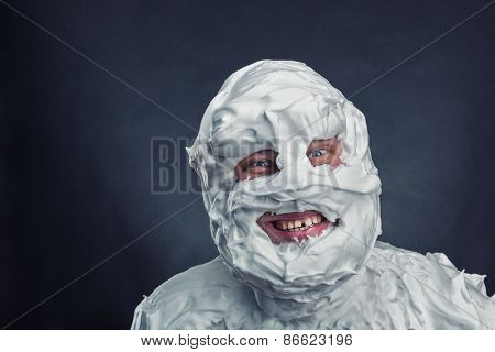 Crazy man with shaving foam on his face over grey background