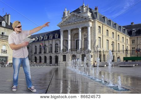 Man with guide book in a hand and classical building in background