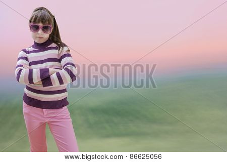 Teenage girl in pink wears sunglasses at sunrise background