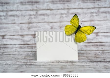 Close up Small Blank White Card with Yellow Green Butterfly at the Upper Right Corner, Emphasizing Copy Space, Standing on Top of a Wooden Table.