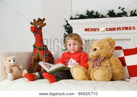 Little Girl Reading A Book In His Toys Christmas Decorations