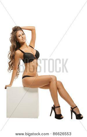 Gorgeous lingerie model posing sitting on cube