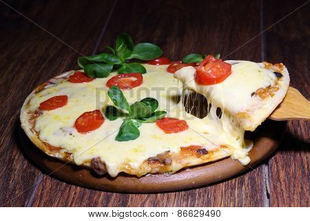 Piece Of A Pizza With The Fused Cheese On A Wooden Shovel