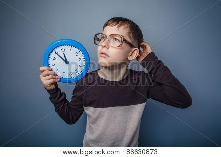 teenager boy of European appearance with glasses holding a clock