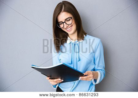 Smiling businesswoman holding folders over gray background. Wearing in blue shirt and glasses. Looking at folder