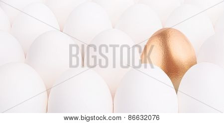 gold Easter egg between many white eggs