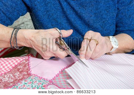 Close-up Of The Hands Of A Seamstress With Scissors