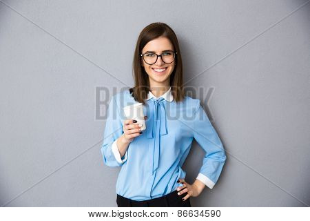 Portrait of a cheerful businesswoman holding cup with coffee over gray background. Wearing in blue shirt and glasses. Looking at camera