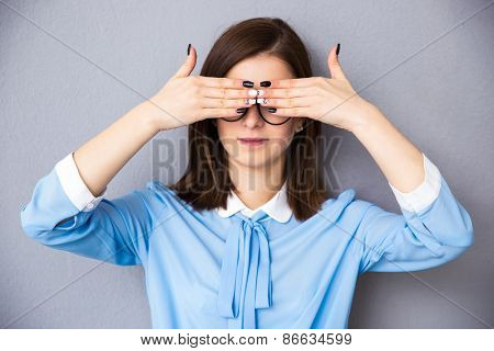 Businesswoman covering her eyes over gray background. Wearing in blue shirt