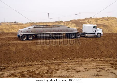 Spreader distributes soil over construction job site