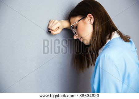 Businesswoman with depression expression over gray background. Leaning on the gray wall.