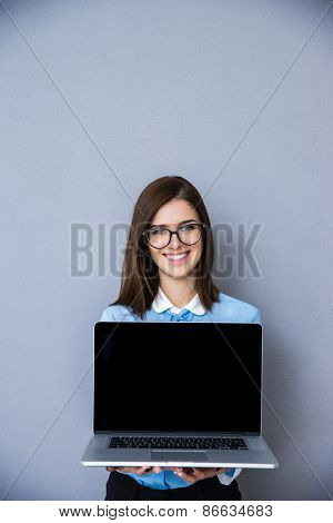 Smiling businesswoman showing blank laptop display over gray background. Looking at camera. Wearing in glasses and blue shirt
