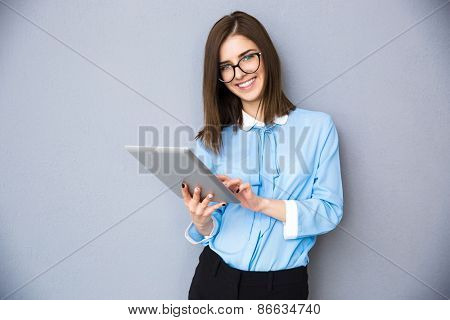 Smiling businesswoman standing with tablet computer over gray background. Wearing in blue shirt and glasses. Looking at camera