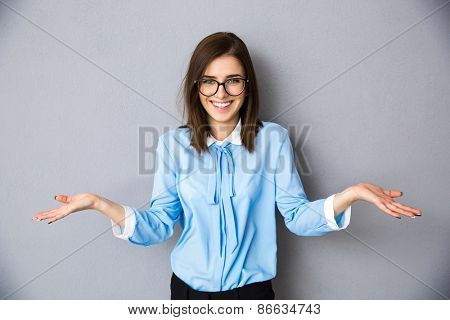 Smiling businesswoman in gesture of asking over gray background. Looking at camera. Wearing in blue shirt and glasses