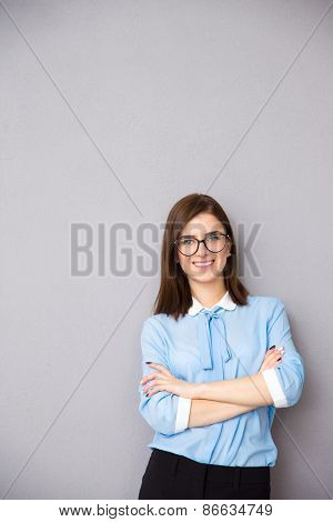Portrait of a smiling businesswoman in glasses standing over gray background with arms folded. Looking at the camera