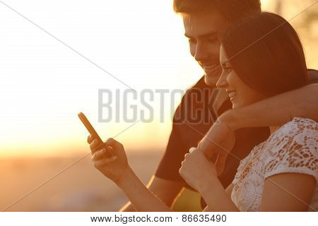 Couple Using A Smartphone In A Sunset Back Light