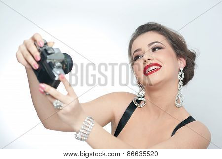 Beautiful young girl with creative make-up and hair style taking photos of herself with a camera